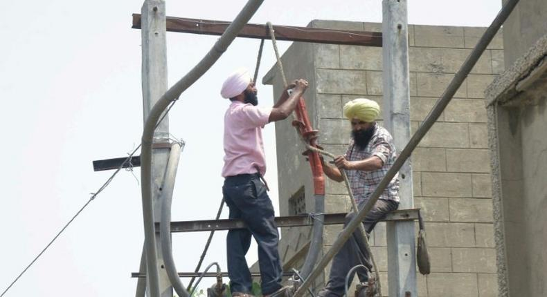 Workers repair an electricity pylon in Amritsar in April: India's transmission system is in poor shape