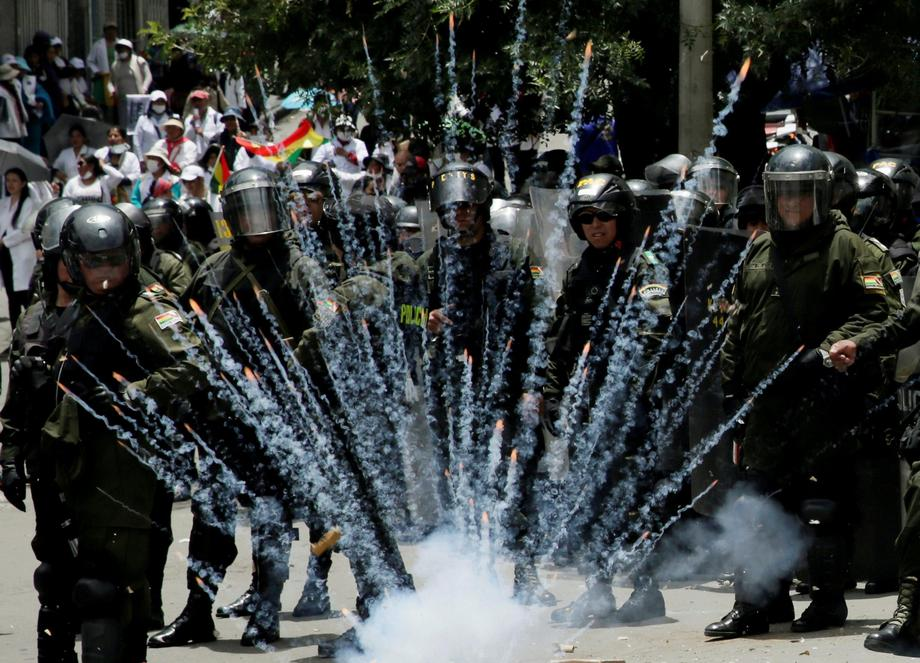 A firecracker explodes next to riot police officers during a protest rally against Bolivia's governm