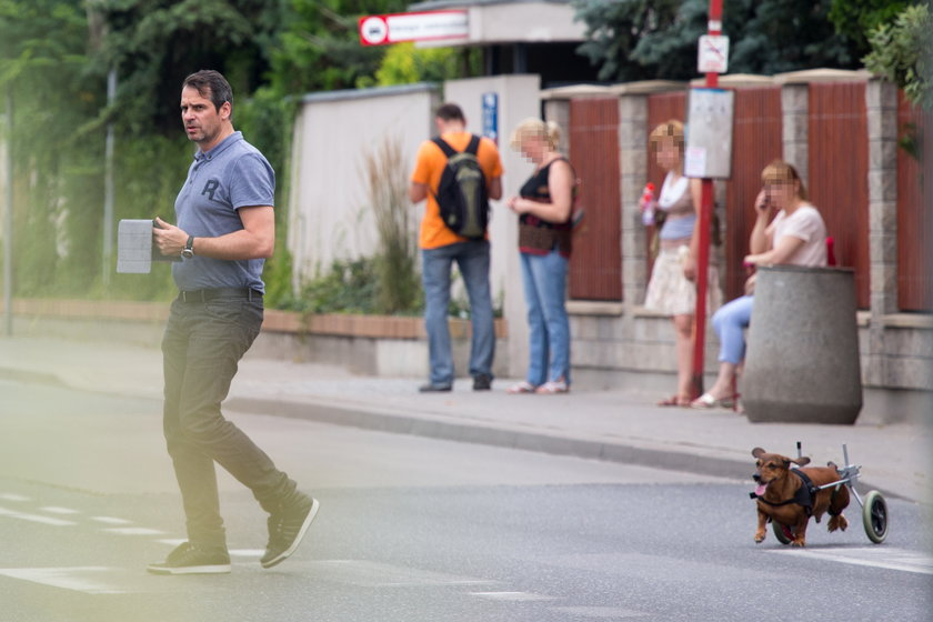 Paweł Deląg z psem na wózku inwalidzkim na spacerze