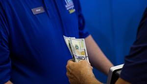 A bettor hands cash to a teller to place a bet on the first day of legal sports betting in  New Jersey in 2018.