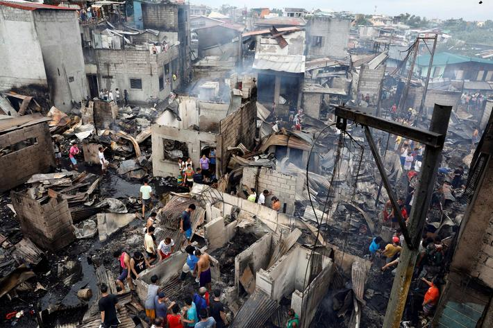 Fire victims gather on the ruins of houses after a fire razed a residential neighbourhood in Malabon