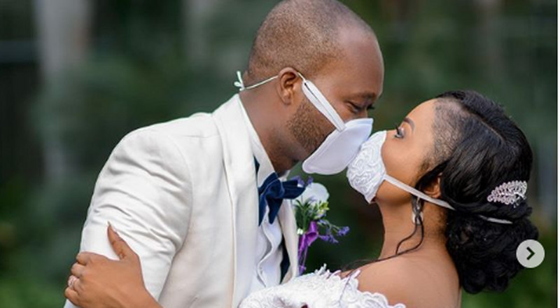 A touching photo shows how two newlyweds shared their first kiss through face masks.