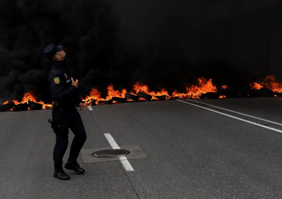 A member of riot police walks in front of a flaming barricade during a May Day rally in Gijon