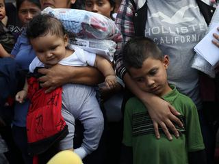 Children of undocumented immigrant families react as they are released from detention at a bus depot