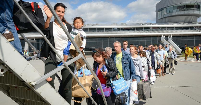Kolejka pasażerów stojąca przed samolotem na lotnisku w Łodzi