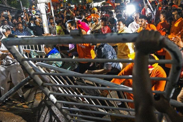More than a hundred people were arrested in street battles that forced Amit Shah to leave an election rally under armed guard