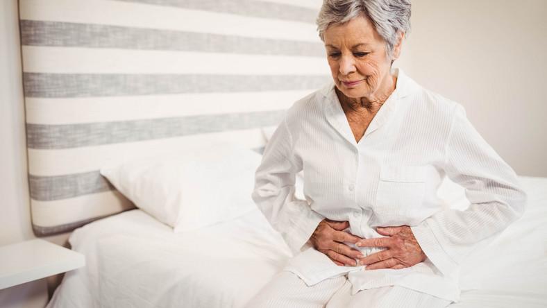 Starsza kobieta trzyma się za brzuch