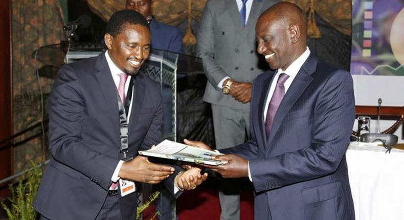 File image of Mwangi Kiunjuri receiving a report from DP Ruto during the opening of the comprehensive agriculture development programme at Safari Park hotel in Nairobi on June 12, 2019.