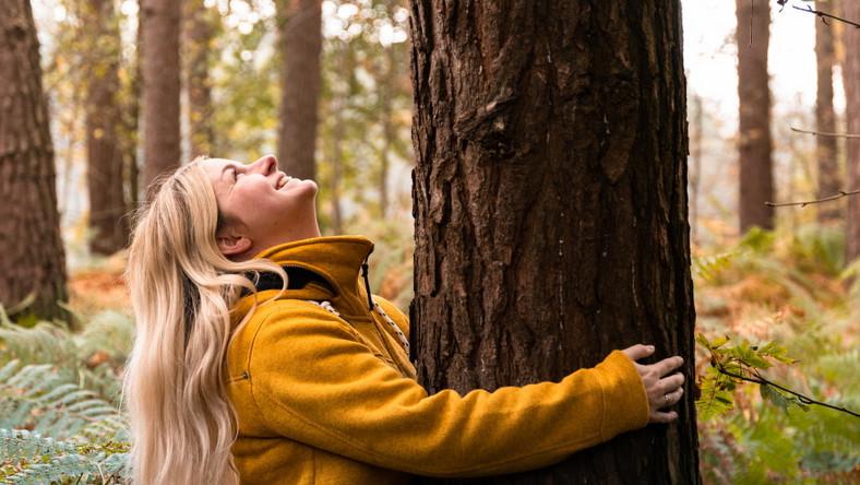 Kobieta w lesie obejmuje drzewo