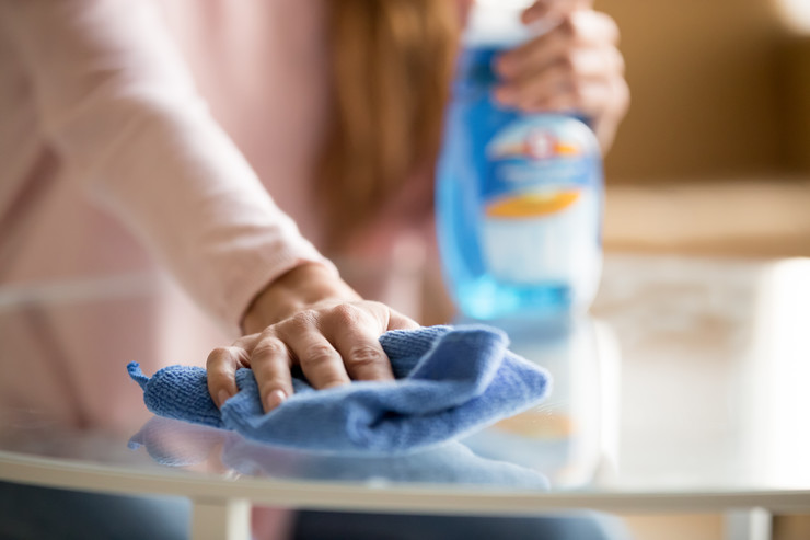 stock-photo-close-up-of-female-housekeeper-specialist-hold-blue-duster-cleaning-glass-table-perform-1437249008