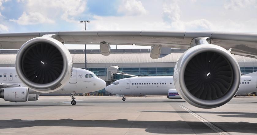 Dwa samoloty Boeinga na tle skrzydeł Airbusa A380. Airbus i Boeing to podniebni giganci w przemyśle lotniczym