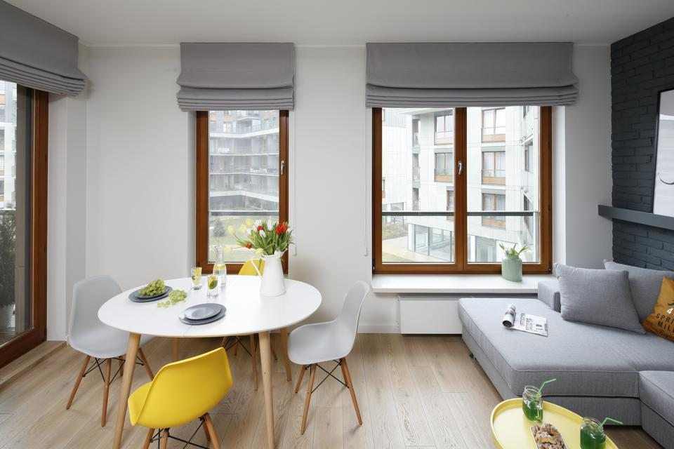 W części wypoczynkowej główną rolę gra nowoczesna i wygodna narożna kanapa w modnym odcieniu szarości, który stanowi doskonałe tło dla wyrazistych stylowych dodatków.