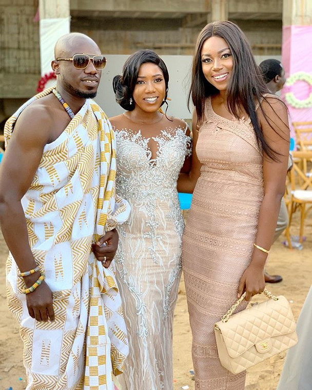 Yvonne Nelson poses with bride and groom