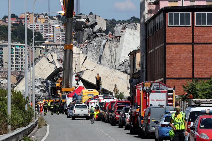 Firefighters and rescue workers stand at the site of a collapsed Morandi Bridge in the port city of
