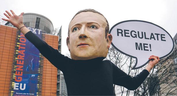"""Działacz Avaaz w masce Marka Zuckerberga, prezesa Facebooka, mówiącego: """"Reguluj mnie"""" przed siedzibą Komisji Europejskiej"""