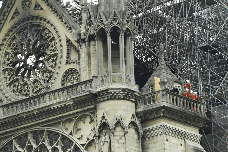 Firefighters surveying the damage from a balcony at Notre-Dame cathedral in Paris on Tuesday, when the fire was extinguished nearly 15 hours after it started
