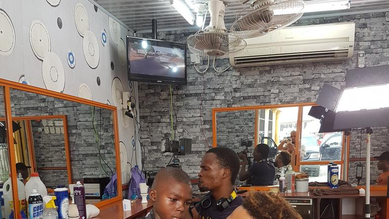 Lekan giving Pulse Tv's Chuey a haircut while Chris records them.