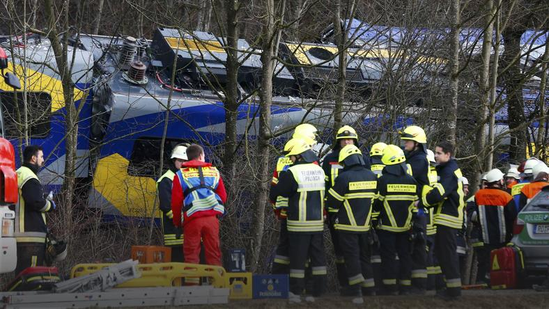 Members of emergency services stand next to a crashed train near Bad Aibling