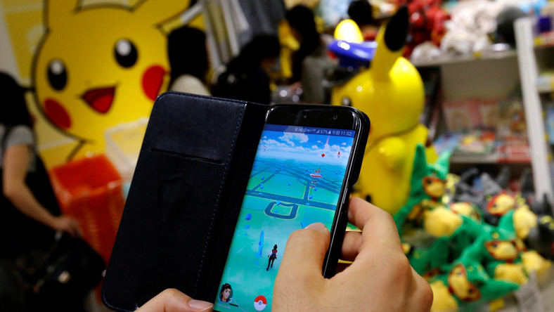 "A man plays the augmented reality mobile game ""Pokemon Go"" by Nintendo in front of a shop selling Pokemon goods in Tokyo"