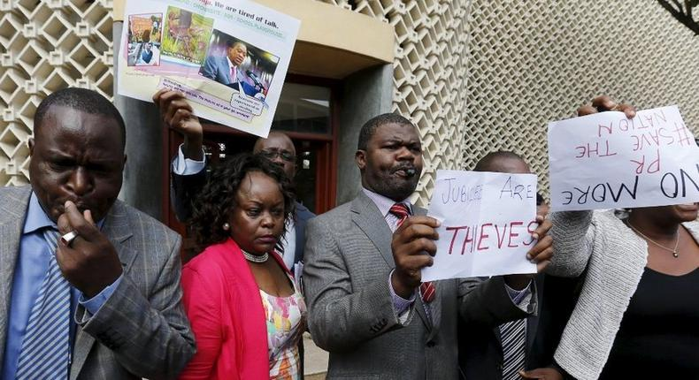 Kenyan Opposition Members of Parliament blow whistles and hold placards in protest as they leave the National Assembly during President Uhuru Kenyatta's annual State of the Nation address at the Parliament Buildings in Nairobi, March 31, 2016.