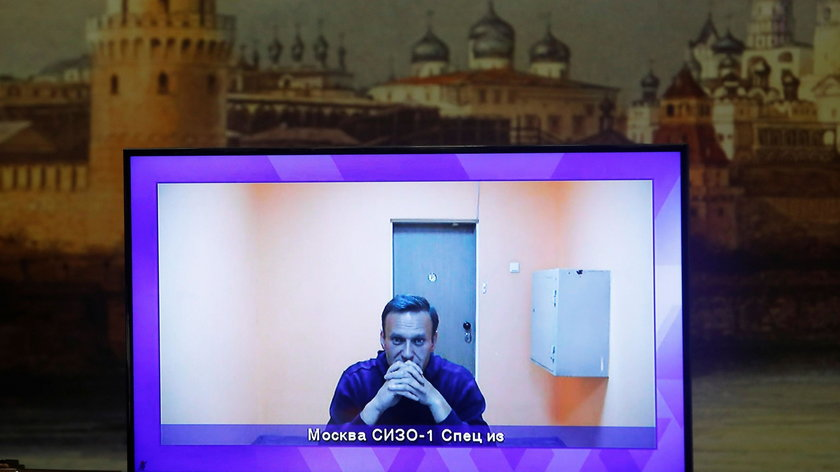 Russian opposition leader Alexei Navalny is seen on a screen via a video link during a court hearing