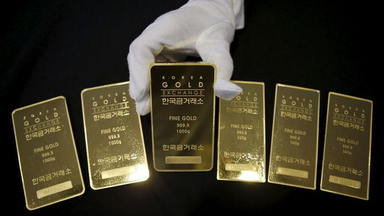 An employee poses for photographs with gold bars at the Korea Gold Exchange in Seoul, South Korea, July 31, 2015. REUTERS/Kim Hong-Ji/Files
