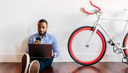 A man works from home next to a bicycle.