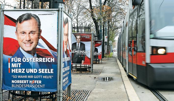 A tramway drives past election campaign posters of Hofer of the FPOe and Van der Bellen, who is supp