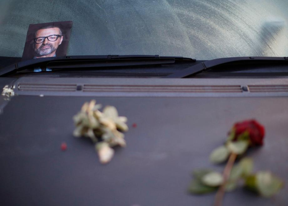 A photograph and rose lie on a car in tribute to singer George Michael outside of his home in north