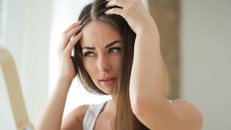 Dojrzała kobieta ogląda włosy w lustrze.