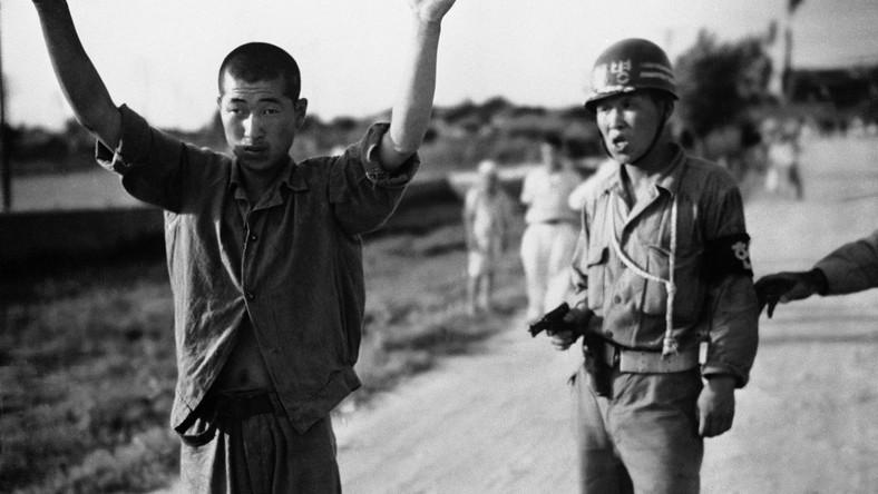 Policjant południowkoreański prowadzi pod bronią północnokoreańskiego jeńca wojennego, 21 lipca 1950 toku
