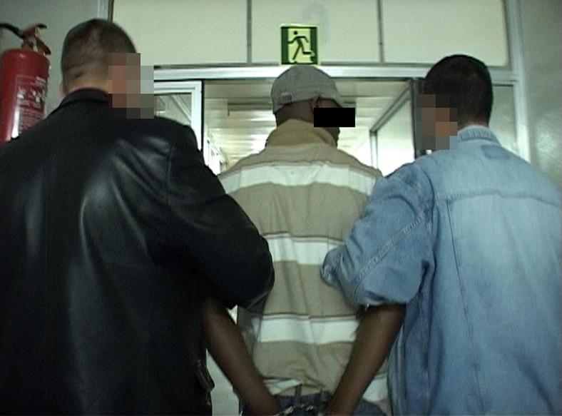 Policjanci prowadzą jednego z zatrzymanych kurierów narkotykowych
