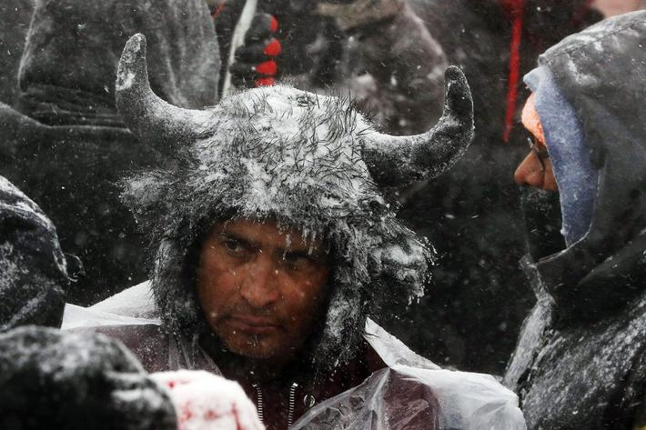 A Native American man stands in the snow during a march with veterans near Backwater Bridge just out