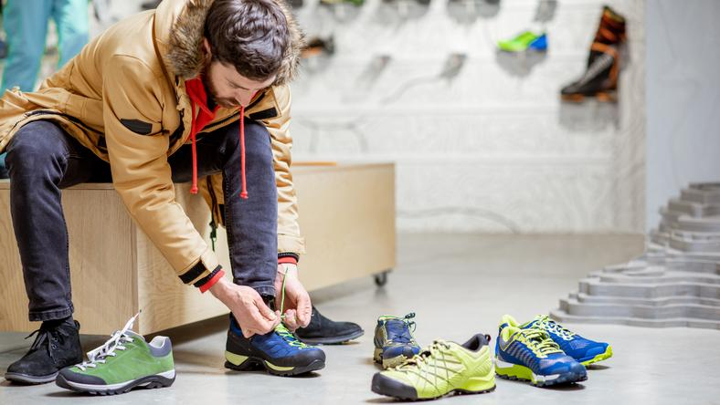 Man trying shoes for hiking in the shop