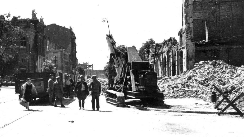 Warszawa, 1946 r. Usuwanie gruzu z ul. Królewskiej. Z lewej strony widoczny fragment budynku Zachęty, z prawej - widoczne kamienice zajmujące narożnik pl. Piłsudskiego