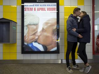 A couple stands next to a poster depicting Dutch politician Geert Wilders and Russian President Vlad