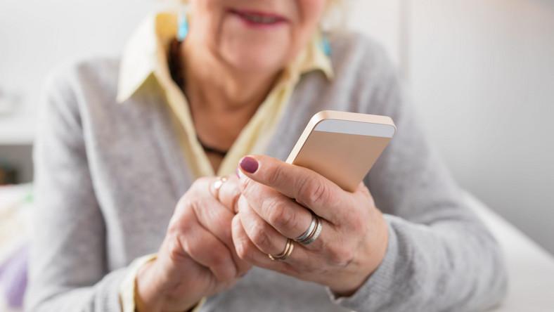 Starsza kobieta używa telefonu