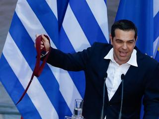 Greek Prime Minister Alexis Tsipras, holds his tie, as he speaks at the parliamentary group of Syriz