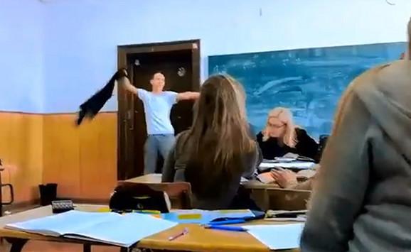 Profesorka : Dok profesorka zapisuje čas, jedan od vandala svlači duks i u ritmu maše njime iznad glave