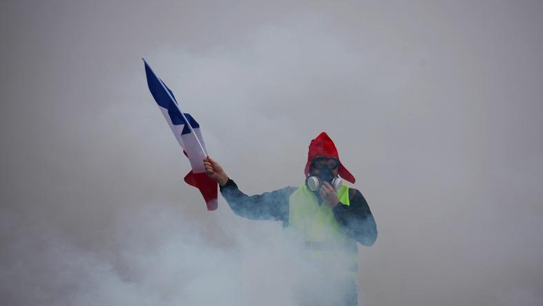 A demonstrator holds a French flag as he walks amid the tear gas during a protest of Yellow vests (Gilets jaunes) against rising oil prices and living costs, on December 1, 2018 in Paris. - Anti-government protesters torched dozens of cars and set fire to storefronts during daylong clashes with riot police across central Paris on December 1, as thousands took part in fresh 'yellow vest' protests against high fuel taxes.