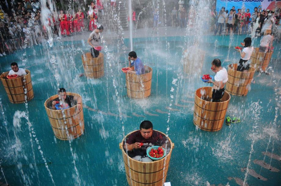 Participants eat chili as they bath in ice water during a chili eating competition in Hangzhou