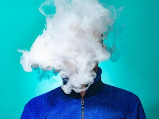 A masked man smoking vape and exhaling