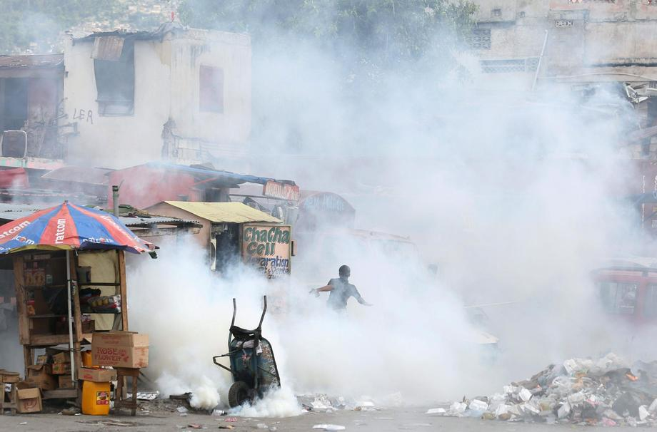 A man runs from tear gas during a protest against tax hikes, in Port-au-Prince