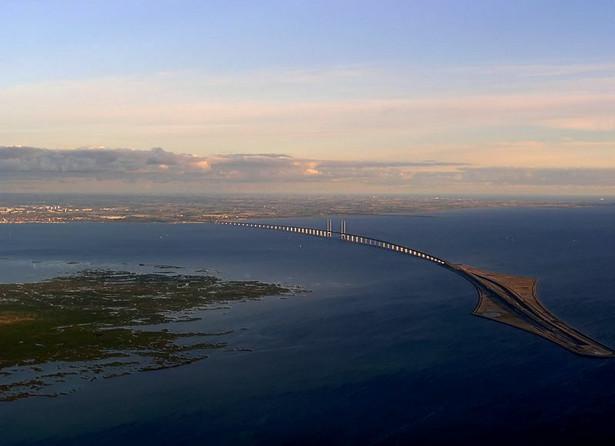 Użytkownicy mają tam do dyspozycji dwie dwupasmowe jezdnie, pod którymi biegną tory kolejowe. Stawki za przejazd samochodem są zaporowe: 46 euro za jednorazówkę albo 33 euro przy zakupie 10-przejazdowego karnetu. Znacznie taniej wychodzi przejazd pociągiem, zwłaszcza z biletem okresowym. Od 2000 r., kiedy most został otwarty, Szwedzi codziennie jeżdżą tędy do pracy, bo stawki w Kopenhadze są korzystniejsze niż w Malmo. Z kolei Duńczycy dojeżdżają mostem-tunelem do swoich domów w szwedzkiej Skanii, bo w Danii ceny nieruchomości są wyższe niż w Szwecji. Most-tunel walnie przyczynił się do wzrostu gospodarczego w rejonie Sund, gdzie wytwarza się łącznie 20 proc. PKB Szwecji i Danii. Budowa przepraw została sfinansowana przez spółkę celowa powołaną przez rządy Danii i Szwecji. Łączny koszt - ponad 20 mld zł. Ta kwota zwróci się nie wcześniej niż w 2035 r. Zdj. Most Oeresund, autor: Dpol, licencja Creative Commons Atıf-Benzer Paylaşım 3.0 Uluslararas