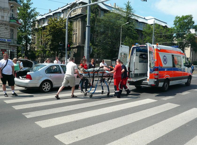 ratownicy wkładają rannego pacjenta do karetki pogotowia