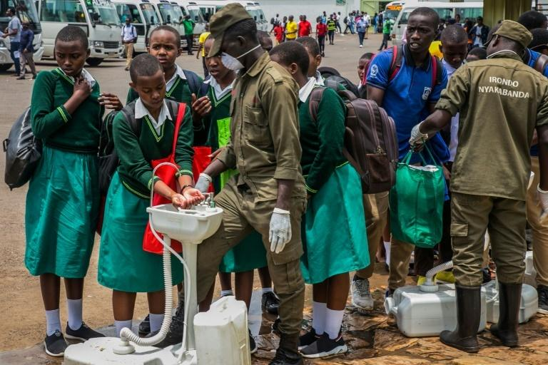 Secondary school students wash their hands at temporary hand washing point in Rwanda