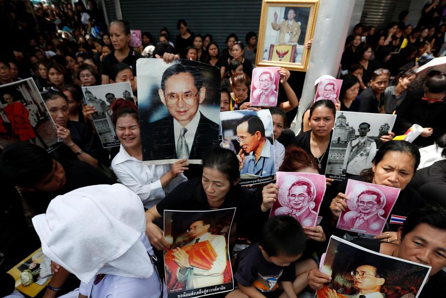 People hold portraits of Thailand's late King Bhumibol Adulyadejas as they wait on the roadside whil