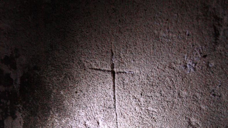 """Wyryty w karcerze krzyż i napis """"Jezu wyratuj"""". W piwnicach domu przy ulicy Świerszcza są dwa takie pomieszczenia. Ciasne, wąskie, pozbawione dostępu światła, z opadającym sufitem. W pozycji wyprostowanej można stanąć w nich tylko przy drzwiach"""