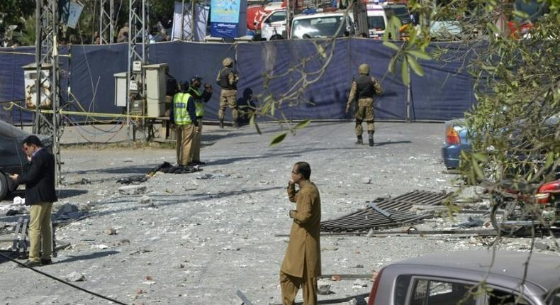 Pakistani security officials examine the site of a bomb attack in blast site in an upscale suburb of Lahore, on February 23, 2017