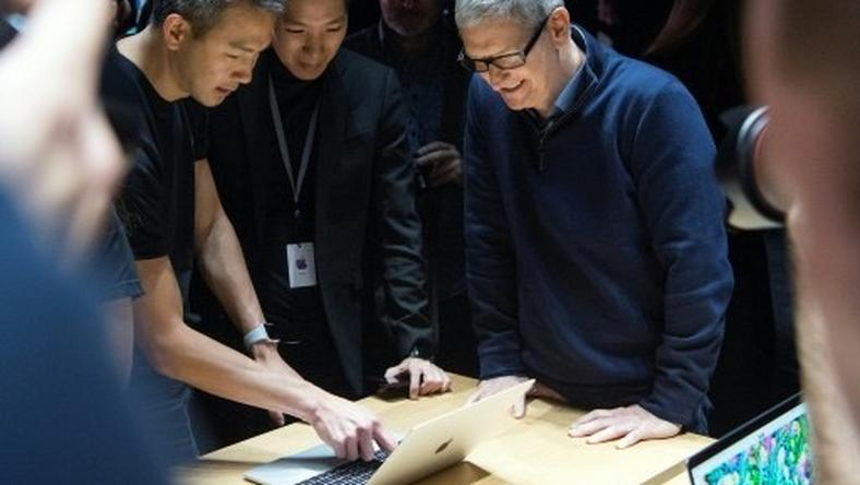 "Apple plans to borrow for its new ""advanced manufacturing"" fund despite having money overseas, because of the tax it would pay if it brought profit home, said CEO Tim Cook (R)"